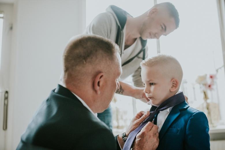 Bruiloft in Leek, bruidsjonker krijgt stropdas om.